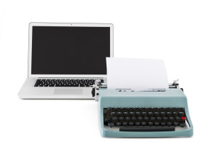 Old typewriter in front of contemporary laptop