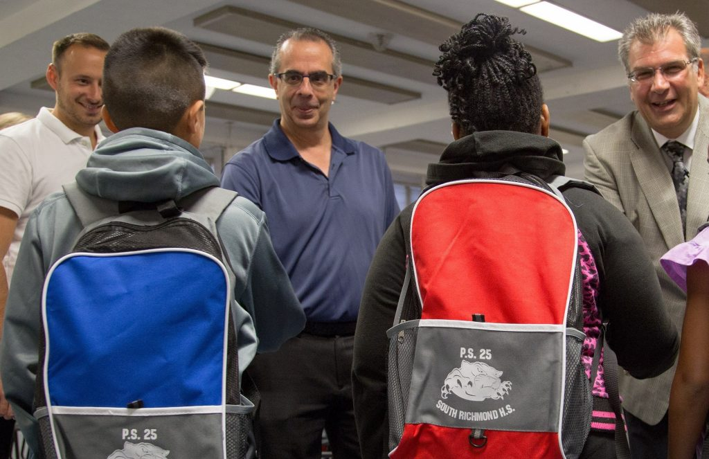 From left, Realtors Kevin Swetsky and Mike Gentilesco work with Assistant Principal Anthony Casella in distributing SIBOR Pack To School supplies in 2015 to students at PS 25/South Richmond High School in Staten Island, N.Y